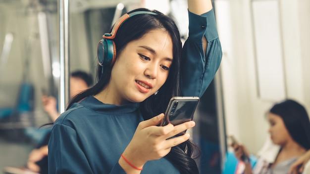 Мобильный телефон молодой женщины в общественном поезде