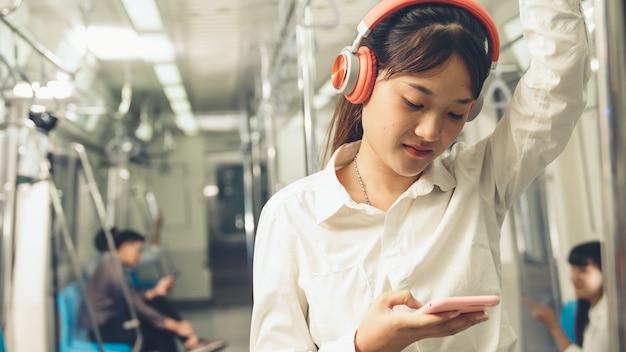 公共の電車の中で若い女性の携帯電話