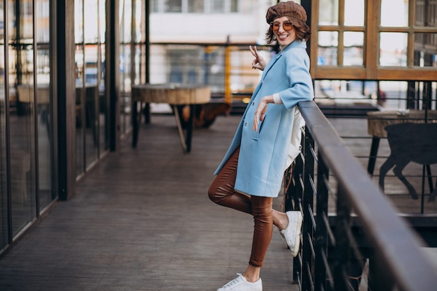 Young woman model in blue coat by the cafe