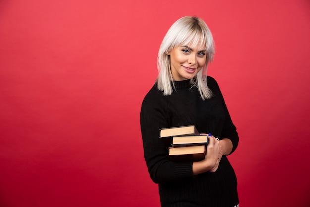 Модель молодой женщины, несущей много книг на красном фоне. фото высокого качества