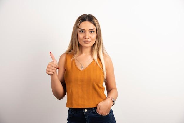 Modello di giovane donna in abiti casual che mostra pollice in su e posa