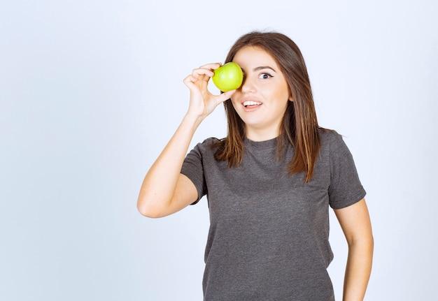 Модель молодой женщины закрыла глаза зеленым яблоком.