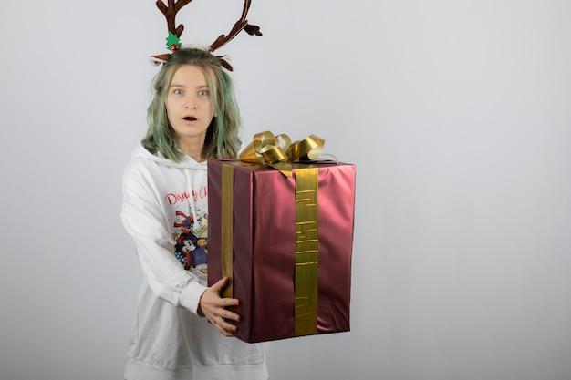 Modello di giovane donna in maschera di corna di cervo che tiene un grande regalo di natale.