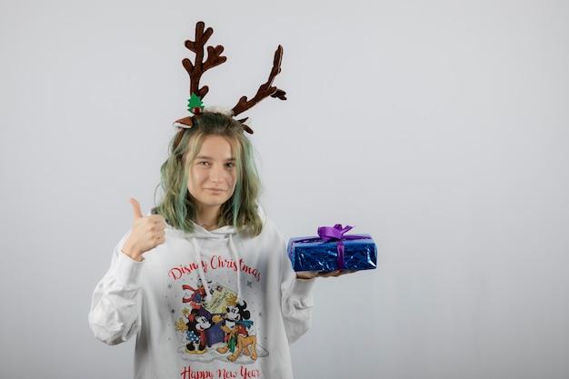 Modello di giovane donna nella maschera di corna di cervo che tiene un regalo e mostra un pollice in su.