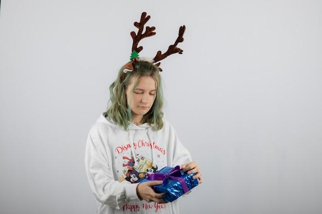 Modello di giovane donna nella maschera di corna di cervo che tiene un regalo.