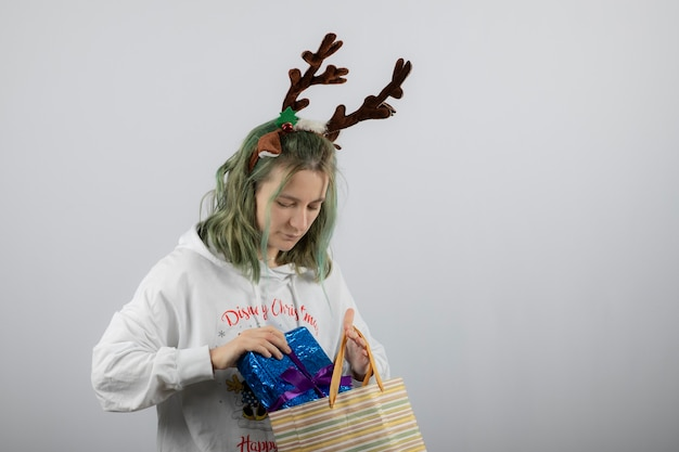 Modello di giovane donna in maschera di corna di cervo che mette un regalo in borsa.