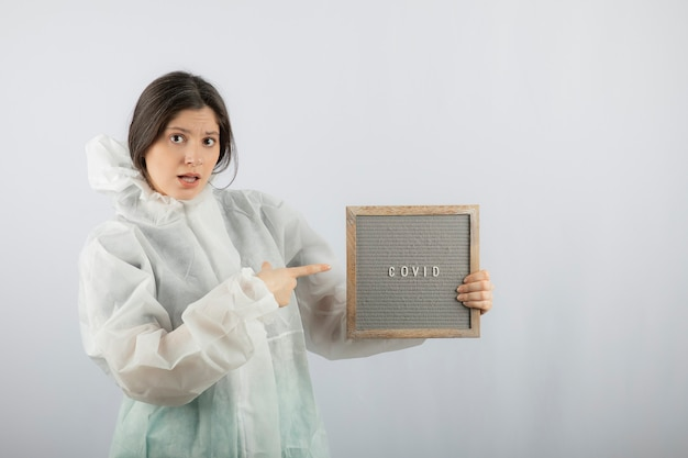 Young woman model in defensive lab coat pointing at a frame.