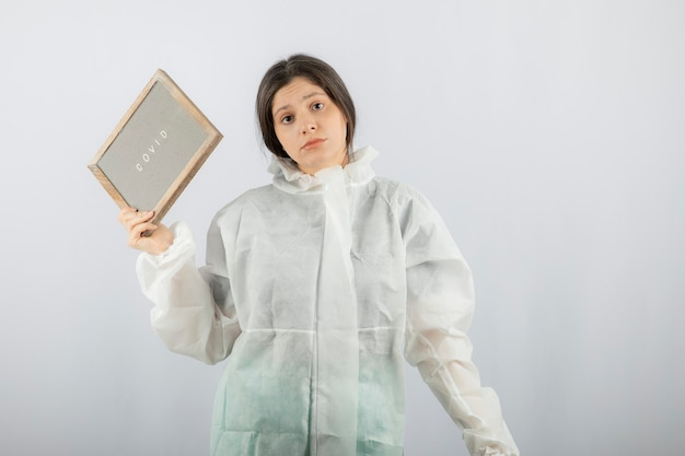 Young woman model in defensive lab coat standing on white wall.
