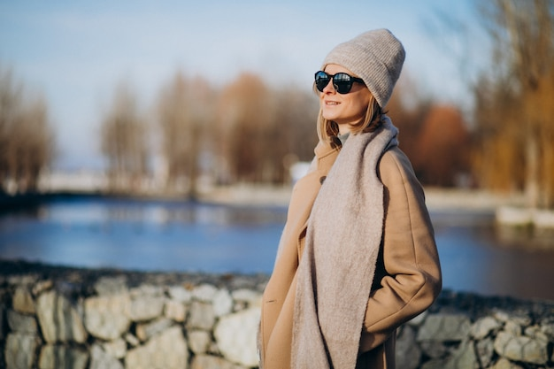 Young woman model dressed in warm coat outside in park