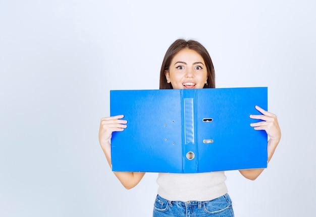 흰 벽에 파란색 폴더를 들고 젊은 여자 모델.