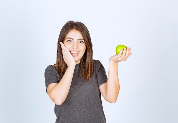 Модель молодой женщины, держащей зеленое яблоко.