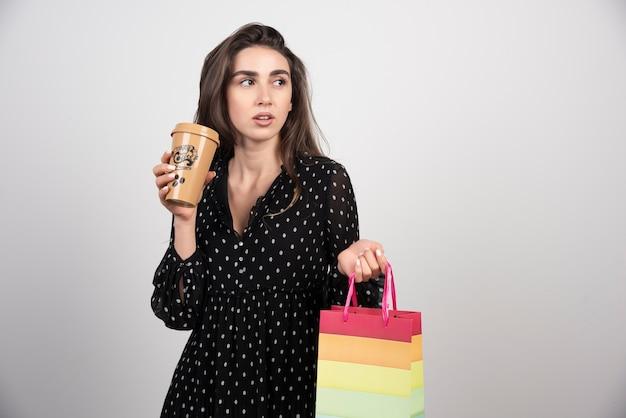 커피 한잔과 함께 쇼핑 가방을 들고 젊은 여자 모델