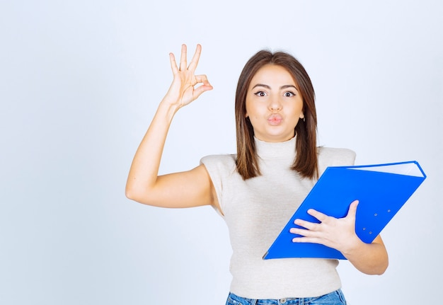 Young woman model holding a blue folder and showing ok gesture over white wall.