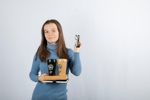 책과 두 잔의 커피를 들고 있는 젊은 여성 모델.