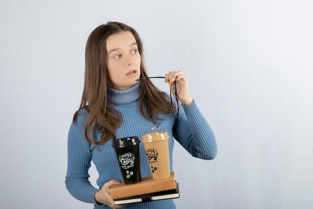 Modello di giovane donna che tiene libri e due tazze di caffè.