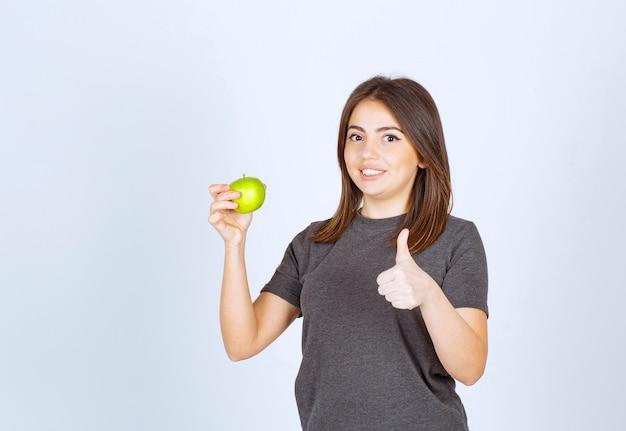 Modello della giovane donna che tiene una mela verde e che mostra un pollice in su.