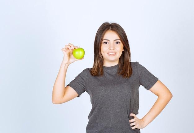 Modello di giovane donna che tiene una mela verde.