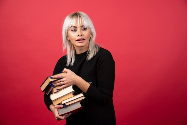 Young woman model holding a lot of books on a red wall.
