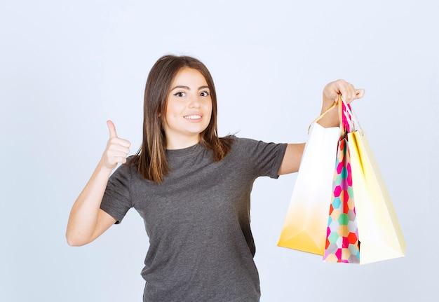 Un modello di giovane donna che tiene in mano molte borse della spesa e mostra un pollice in su.