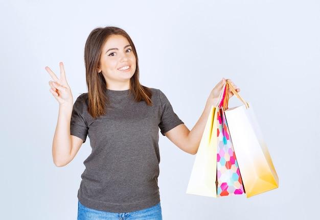 Un modello di giovane donna che tiene in mano molte borse della spesa e mostra il segno della vittoria.