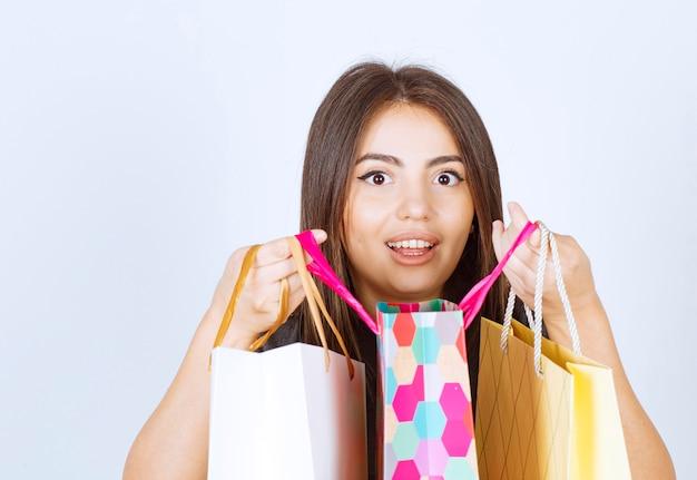 Un modello di giovane donna che tiene un sacco di borse della spesa su sfondo bianco.