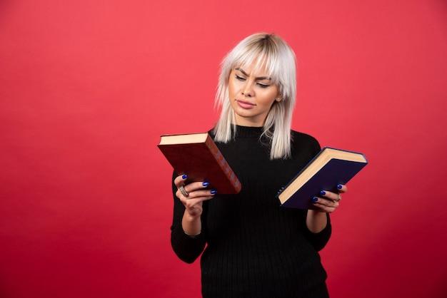 Модель молодой женщины, держащей две книги на красном фоне. фото высокого качества