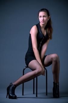 黒のミニのドレスと灰色の背景の上に座っている網タイツの若い女性モデル