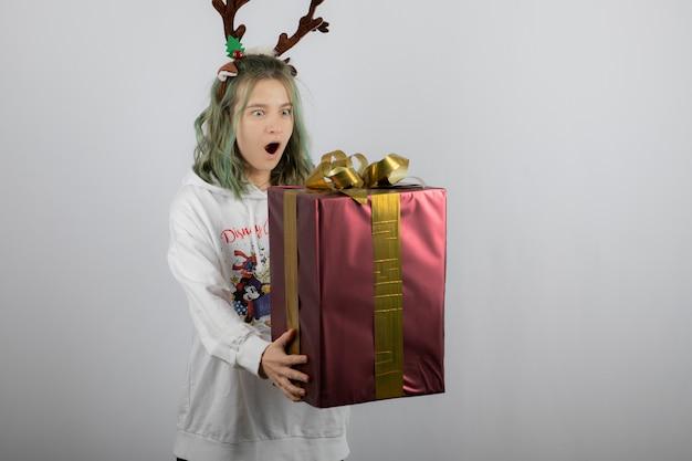 큰 크리스마스 선물을 들고 사슴 뿔 마스크에 젊은 여자 모델.