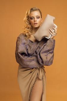 ファッショナブルな服を着た若い女性モデル、ベージュの背景に垂直スタジオ写真。高品質の写真