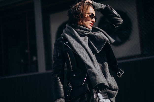 Young woman model in leather jacket outside the street