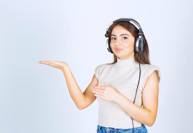 Una giovane donna modella la musica d'ascolto in cuffia e mostra la mano.