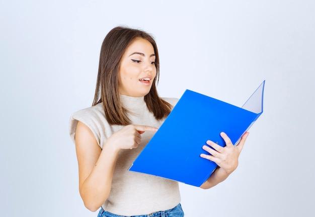 흰 벽에 파란색 폴더를보고 젊은 여자 모델.