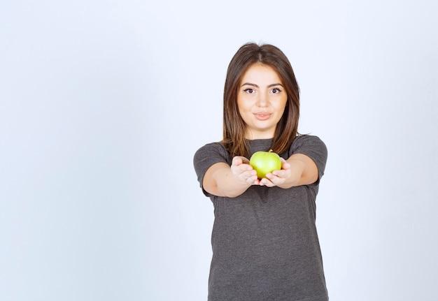 Modello di giovane donna che offre una mela verde.
