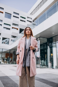 Young woman model in pink coat by the building