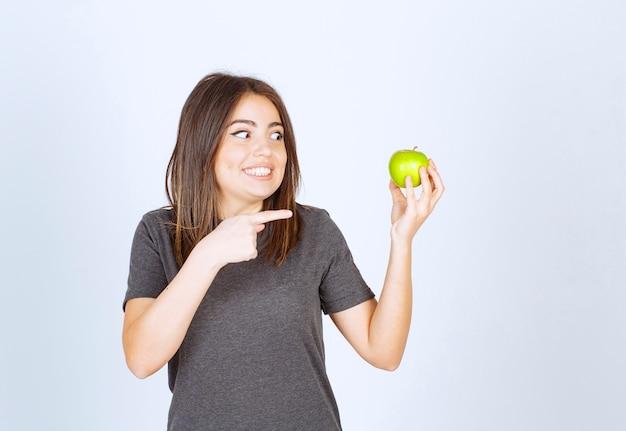Модель молодой женщины, указывая на зеленое яблоко.