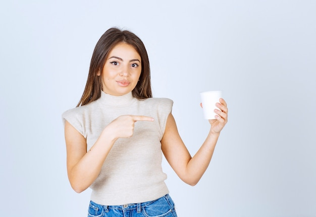 A young woman model pointing at a plastic cup.