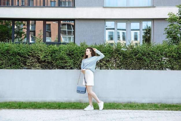 거리 배경에서 여름 옷의 새로운 컬렉션에서 포즈를 취하는 젊은 여성 모델