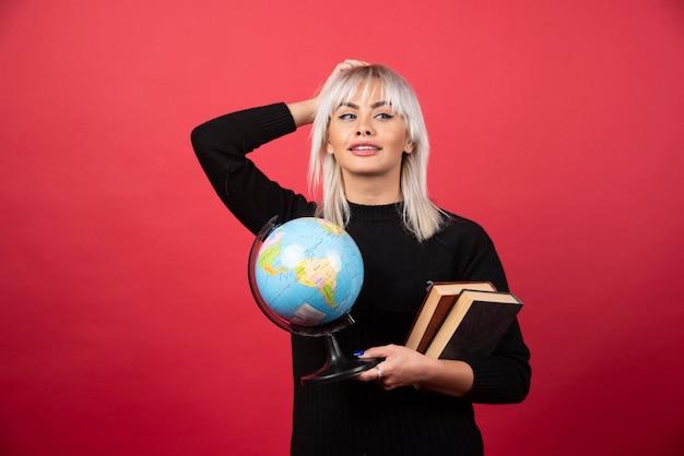 Modello di giovane donna in posa con libri e un globo terrestre su una parete rossa.