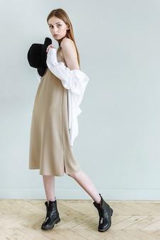 帽子をかぶってポーズをとる若い女性モデル