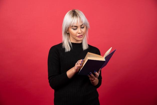 Модель молодой женщины, читая книгу на красном фоне. фото высокого качества