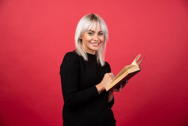 Модель молодой женщины, читая книгу на красной стене.