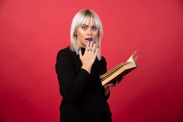 Young woman model reading a book on a red wall.