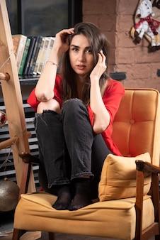 Un modello di giovane donna in camicia rossa seduta e in posa.
