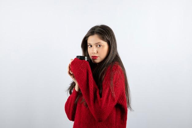 Una giovane modella in maglione rosso con in mano una tazza di caffè