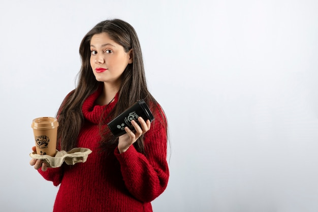 Una giovane modella in maglione rosso con in mano due tazze di caffè