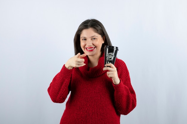 Un modello di giovane donna in maglione rosso con una tazza di caffè che punta alla telecamera