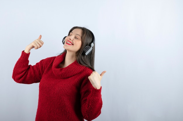 Young woman model in red sweater with headphones showing thumbs up