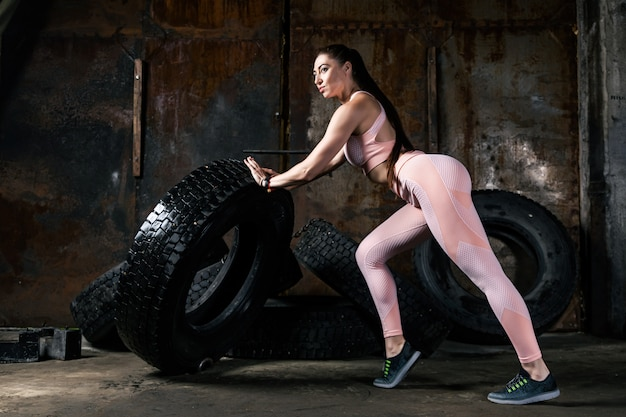 Young woman model in a sporty short top and gym leggings posing and pushing the tire in an old garage
