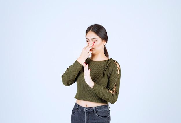 Молодая женщина модель стоя и закрыла нос.