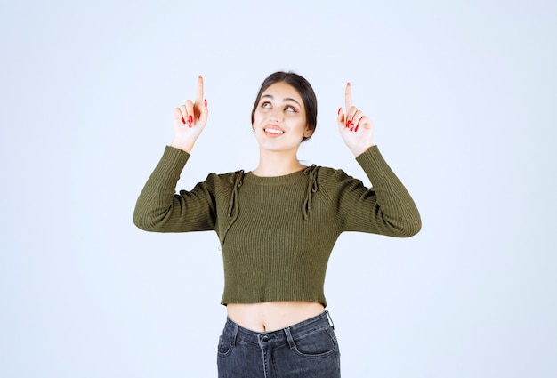Молодая женщина модель стоя и указывая вверх указательными пальцами.